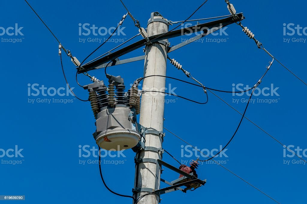 Close-up distribution transformer on concrete power pole stock photo