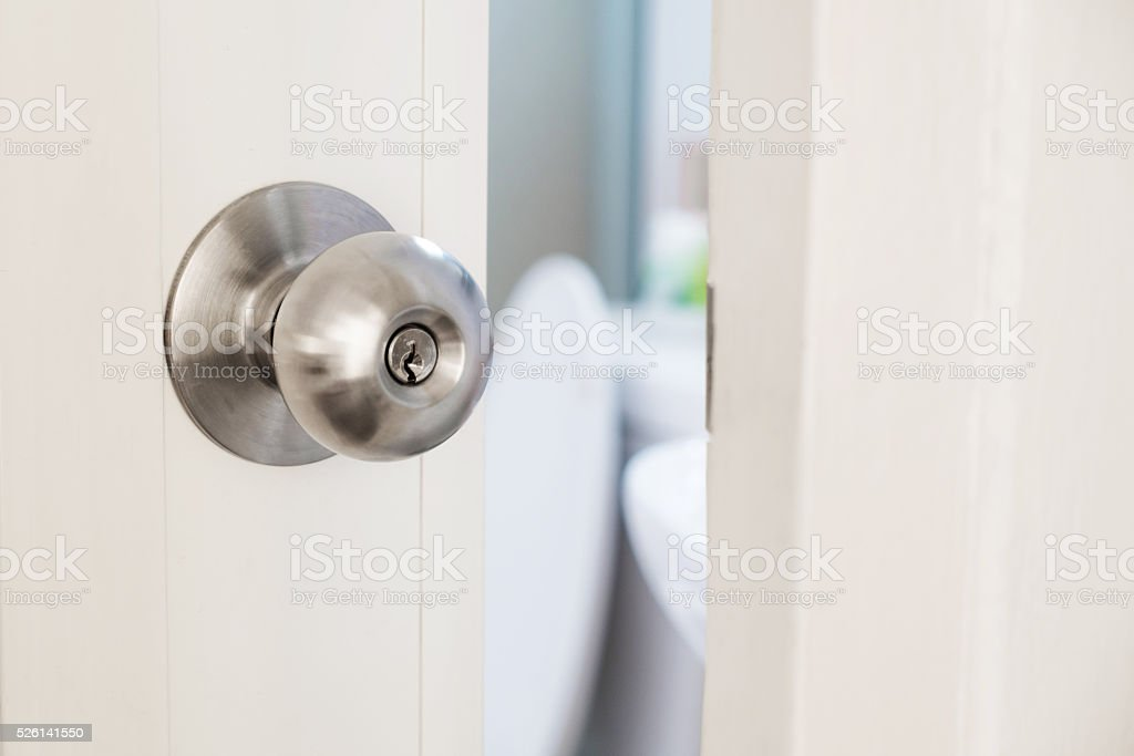 Close-up door stainless door knob, with door open slightly stock photo