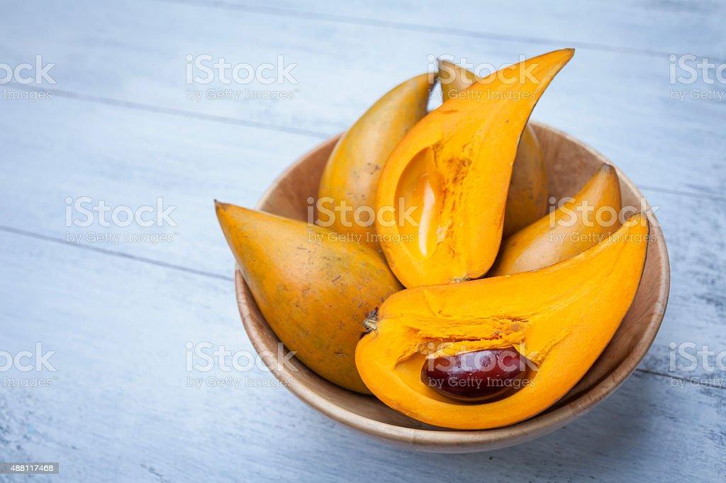 Closeup Eggfruit in wooden bowl stock photo
