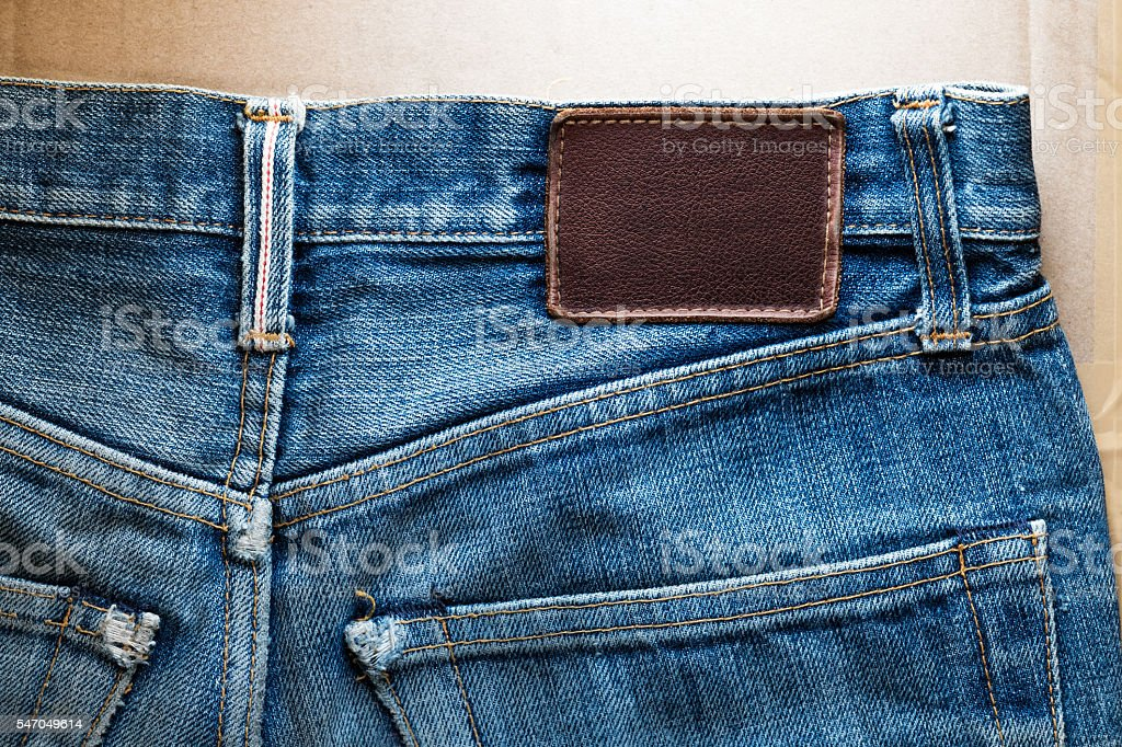 Close-up faded blue jeans back pocket with blank leather tag stock photo