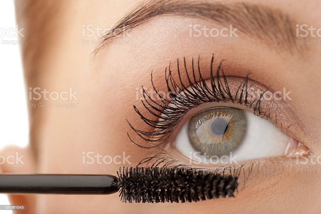 Close-up female applying mascara stock photo