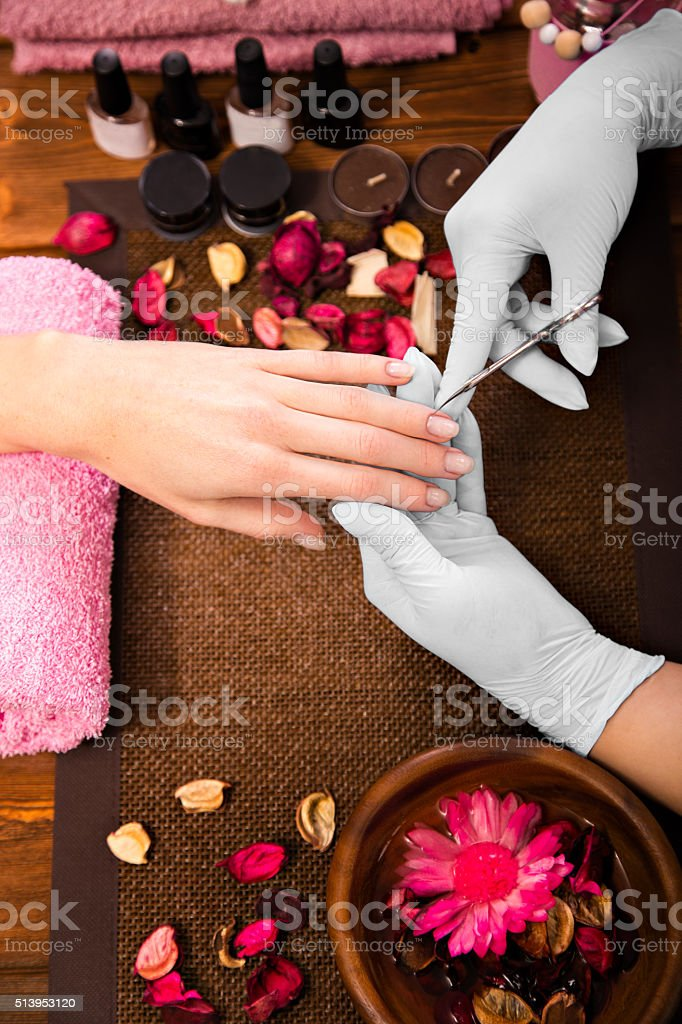 Closeup finger nail care by manicure specialist in beauty salon. stock photo