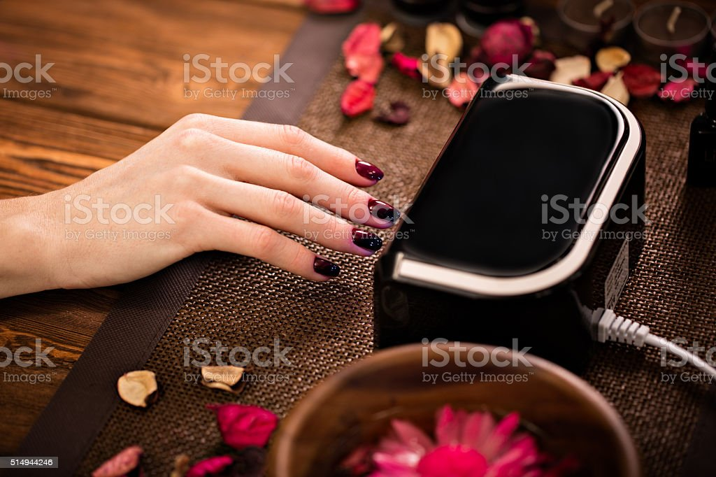 Closeup finger nail care by manicure specialist in beauty salon stock photo