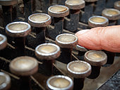 Closeup finger typing vintage typewriter covered with dust