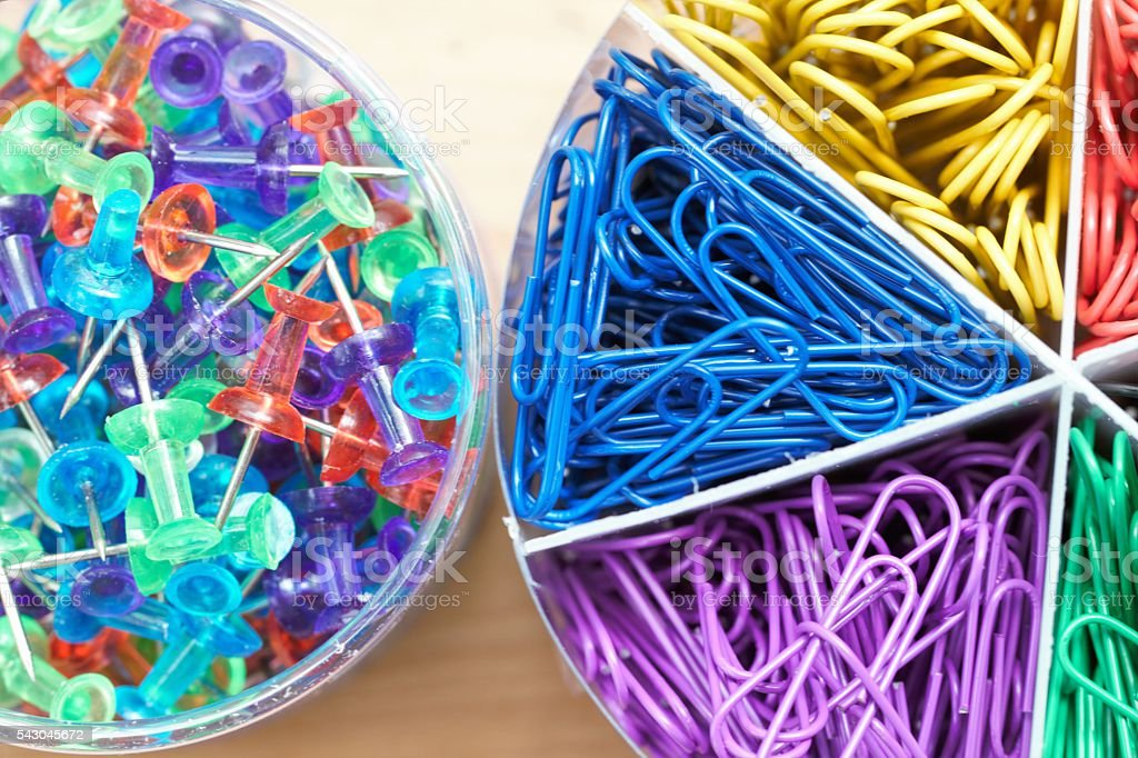 Closeup flatlay of colorful pushpins and paperclips office supplies stock photo