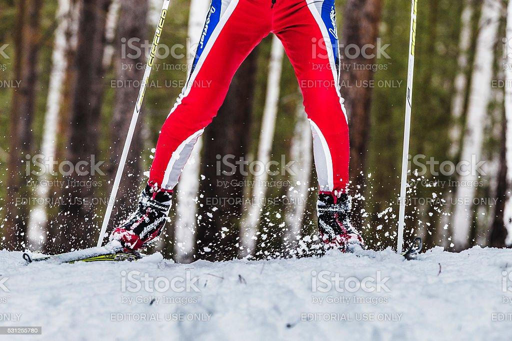 closeup foot male skier sprays snow from under ski stock photo