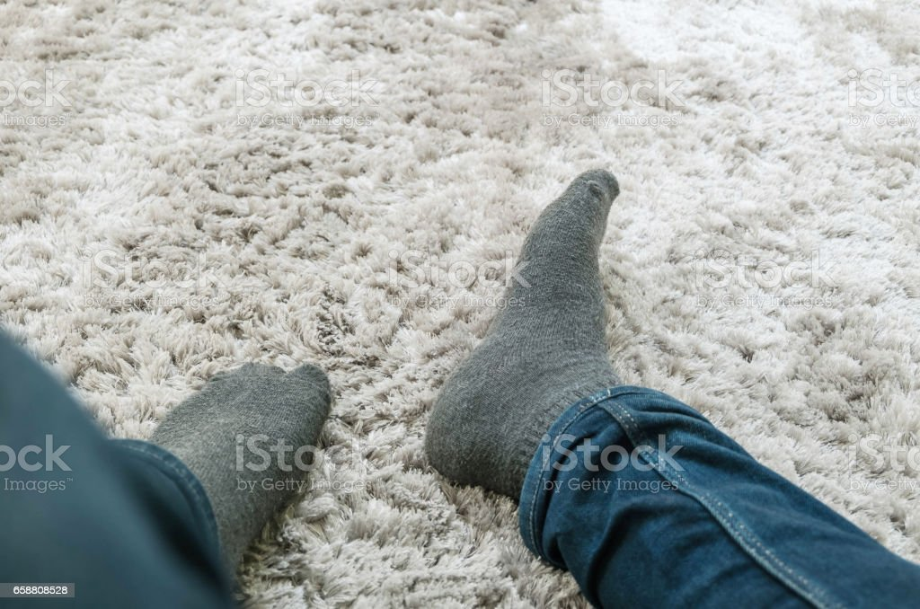 Closeup foot of man sit on gray carpet floor in house textured background with copy space stock photo
