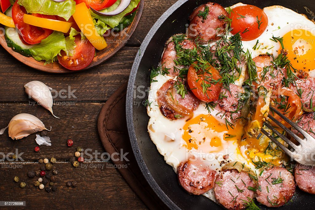 Closeup fried eggs with sausage and tomatoes in frying pan. stock photo