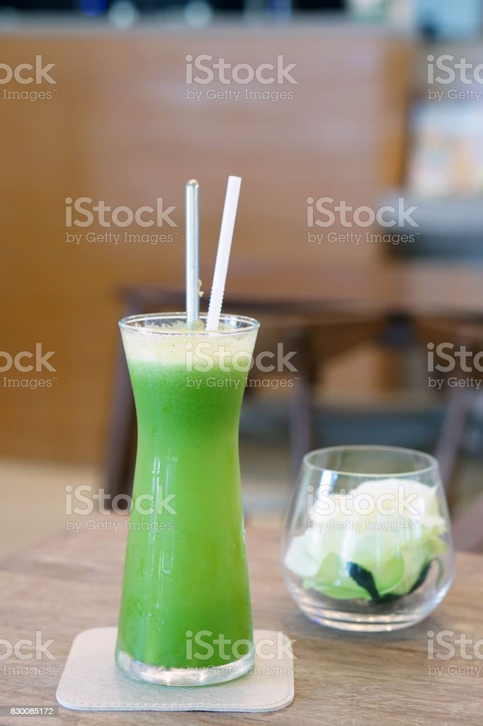 Closeup glass of cold pressed juice on wooden table, Fresh mixed fruits made from Gotu kola, Curcuma, Guava and Pineapple. stock photo