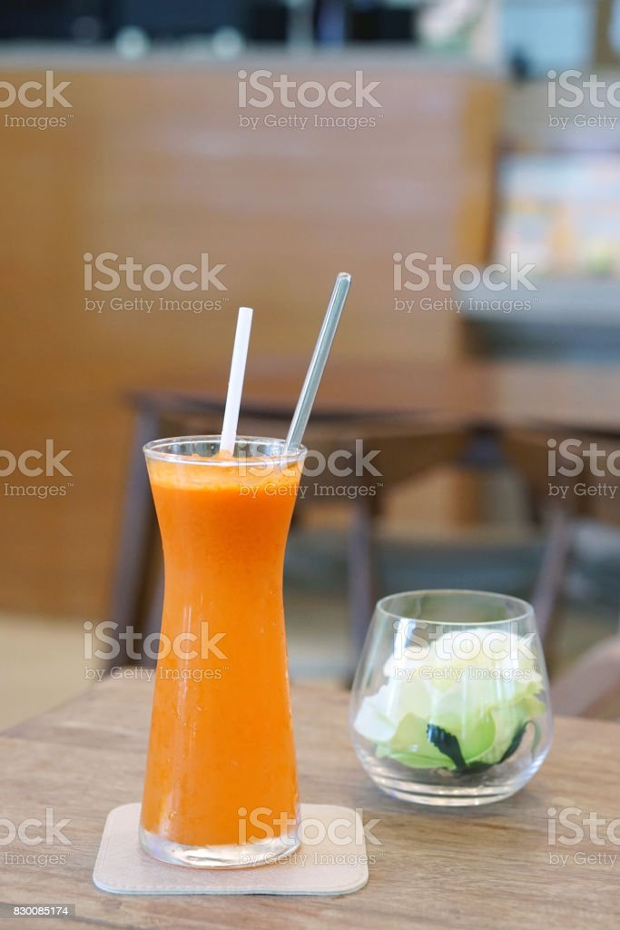 Closeup glass of cold pressed juice on wooden table, Fresh mixed fruits (carrot, passion, fruit, cantaloupe, wolfberry) stock photo