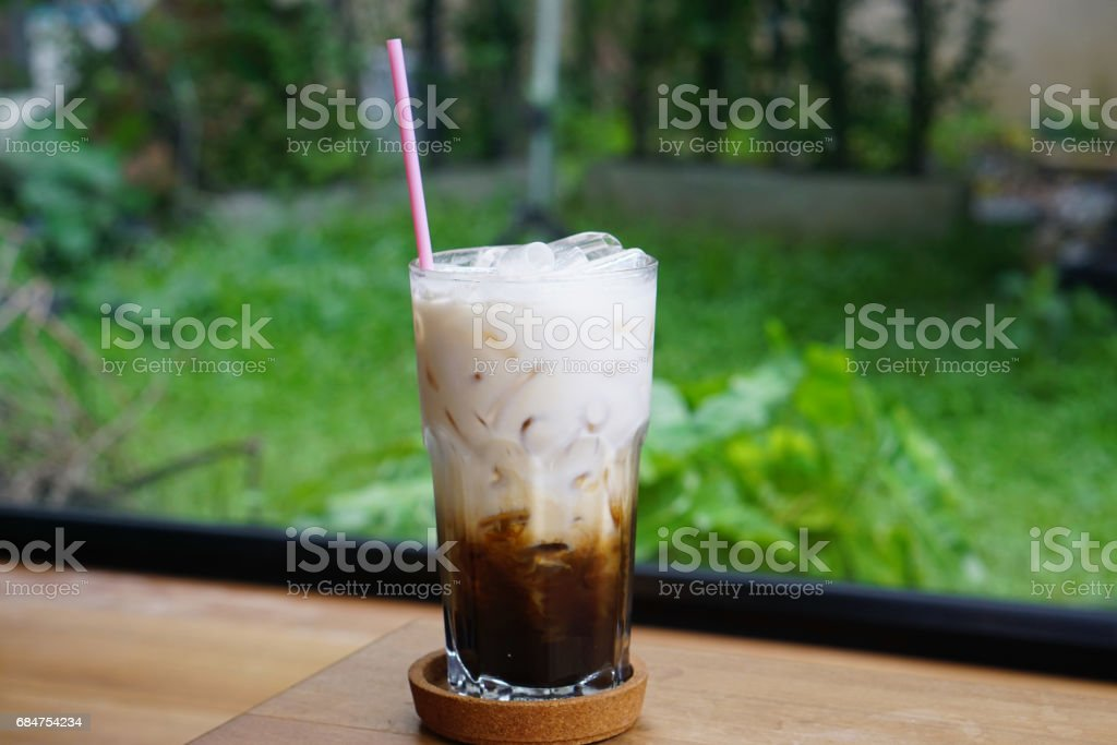 Closeup Glassof of Iced Caramel Macchiato on wooden table, It consists of vanilla syrup, espresso, steamed milk, foam, and caramel drizzle. stock photo