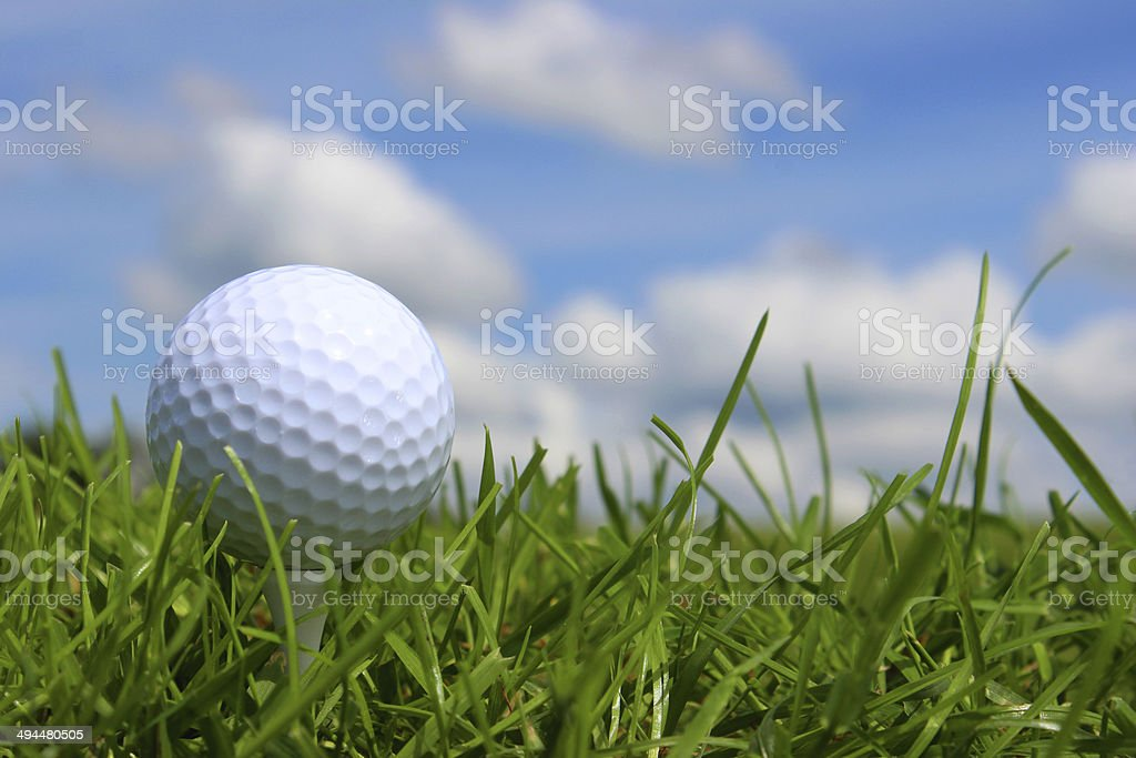 Close-up golf ball in grass on golf course, blue sky stock photo