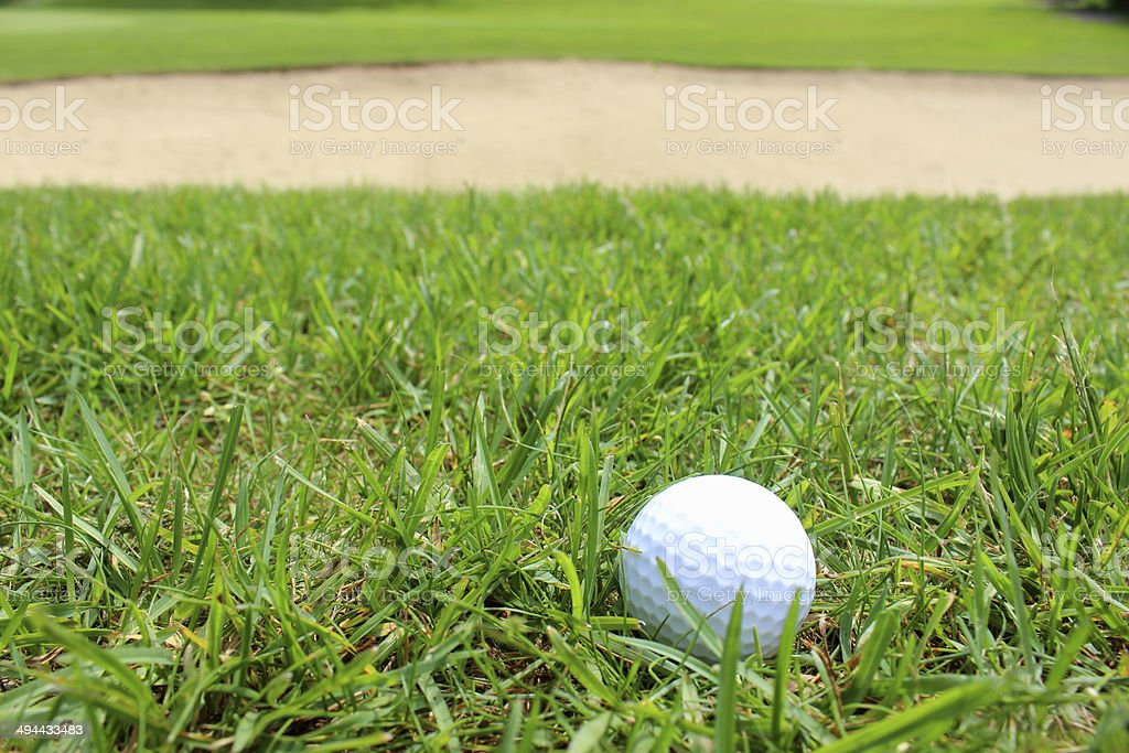 Close-up golf ball in grass on golf course, sandy bunker royalty-free stock photo