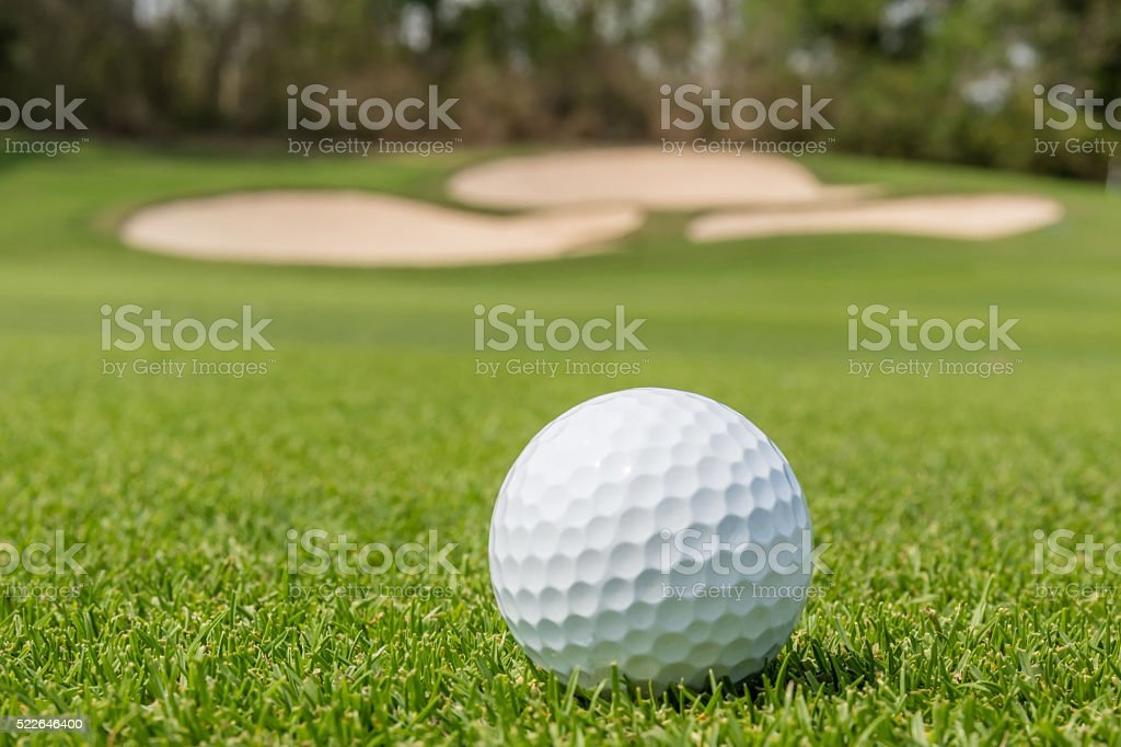 Closeup Golf ball on grass with blurred green course background. stock photo