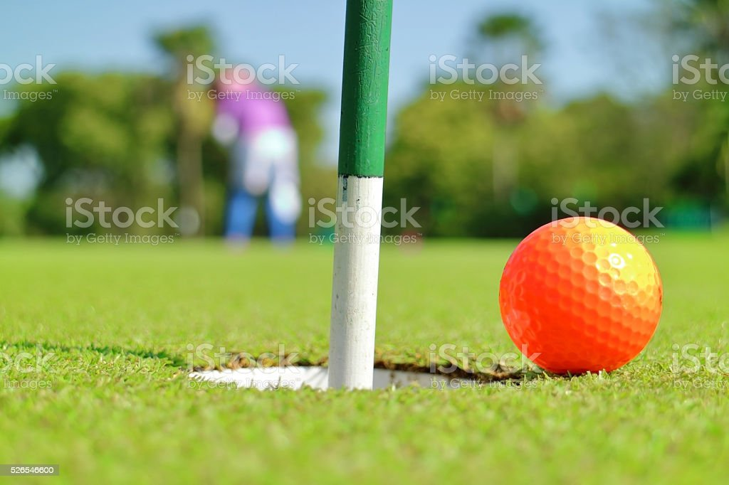 Closeup golf hole and ball on green grass golf course. stock photo