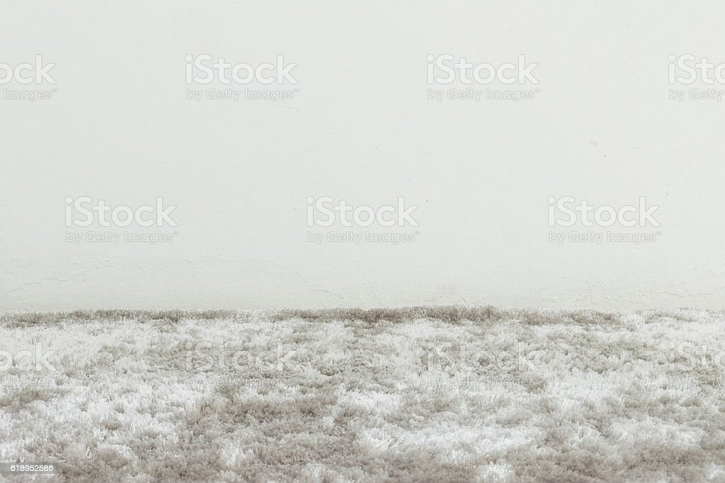 Closeup gray carpet and white cement wall stock photo