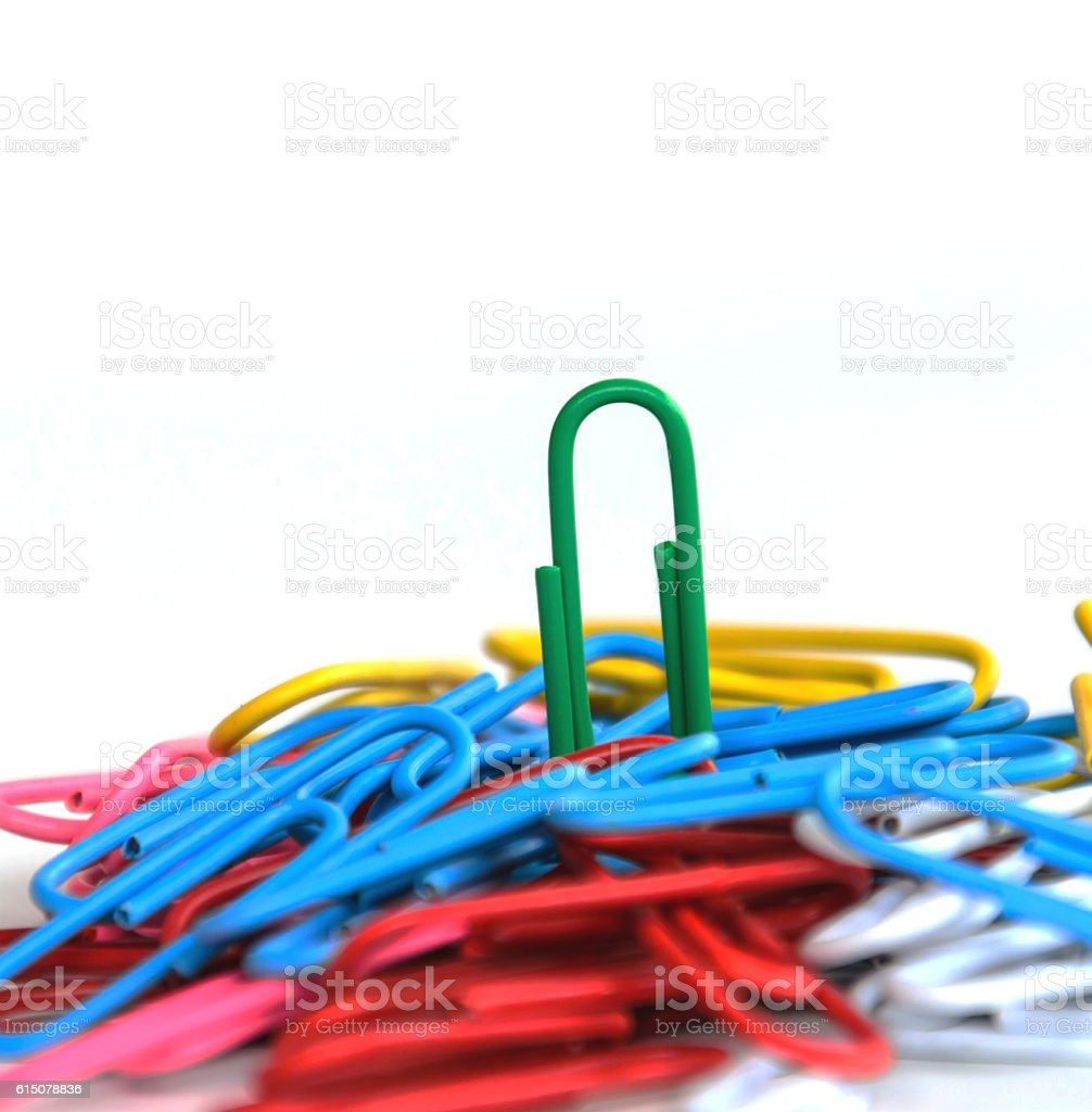 Close-up green clip on top  multi-colored paper clips  concept stock photo