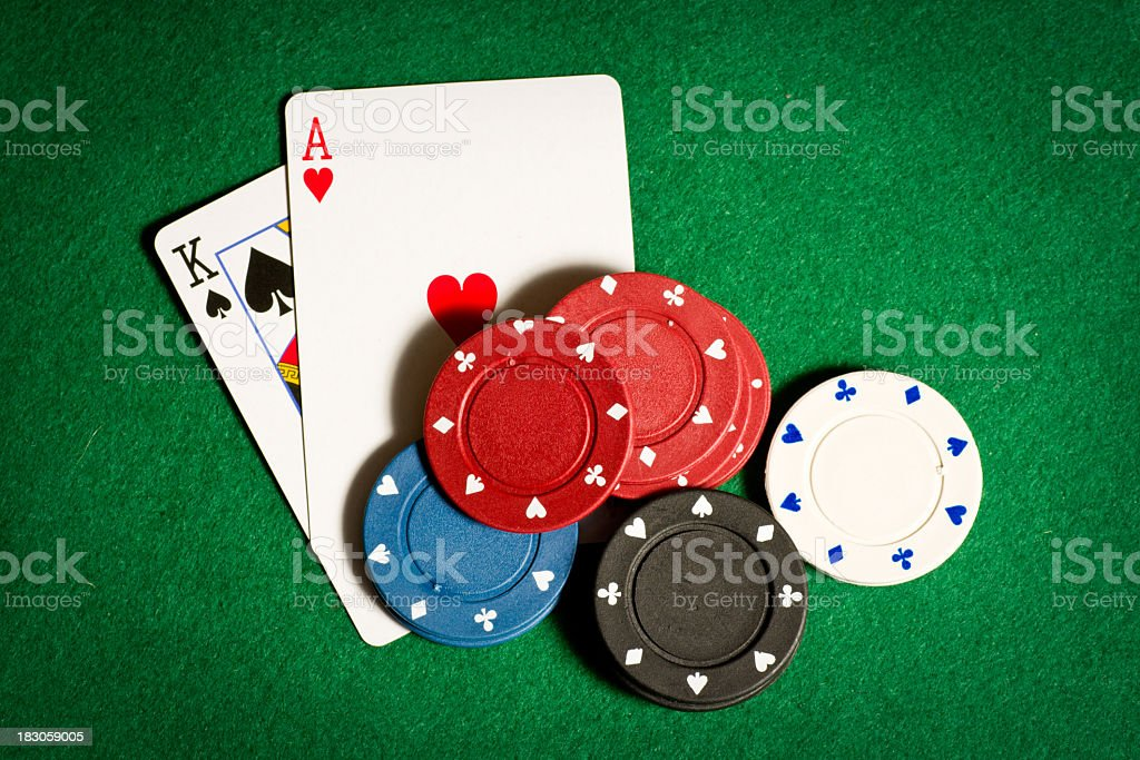 A close-up green poker table with two cards and blank chips stock photo