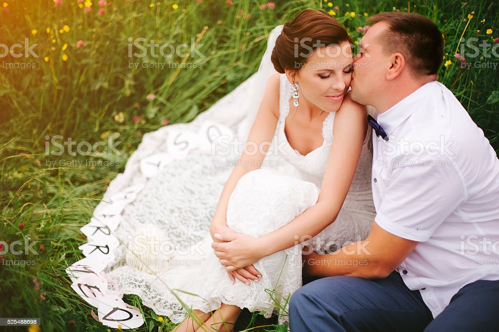 Closeup groom kisses bride on the cheek, sunset meadow stock photo