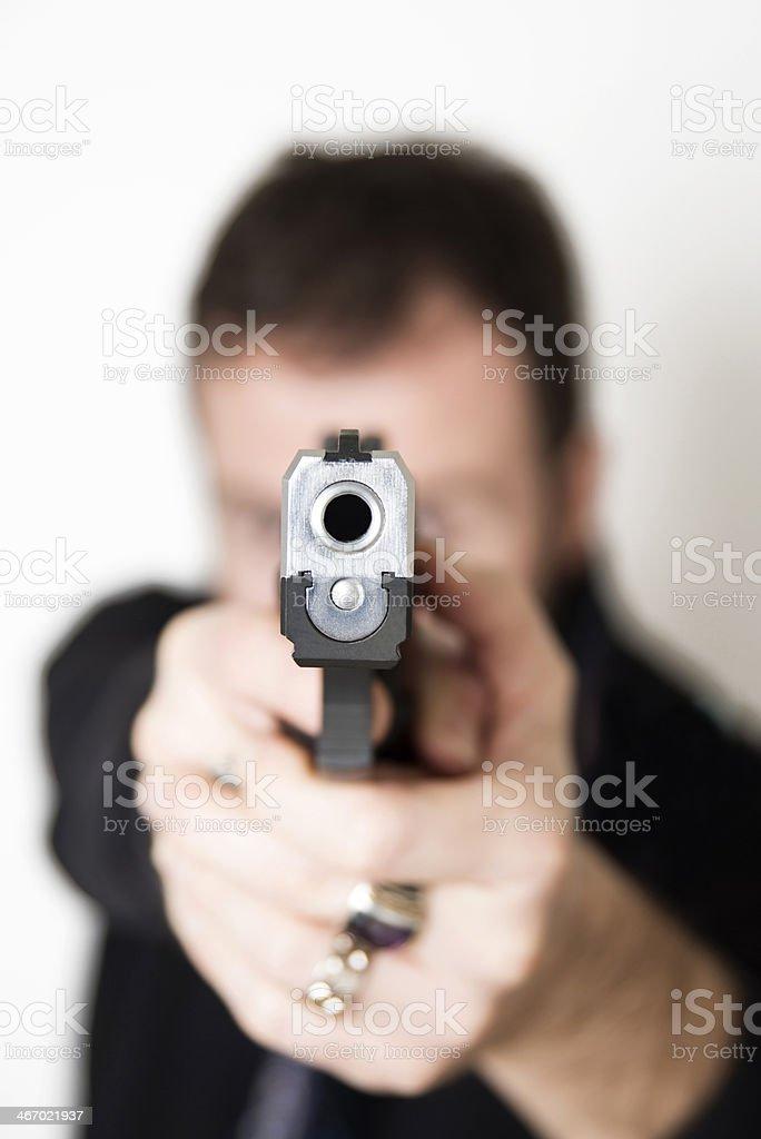 Close-up gunman pointing barrel of gun at the camera stock photo