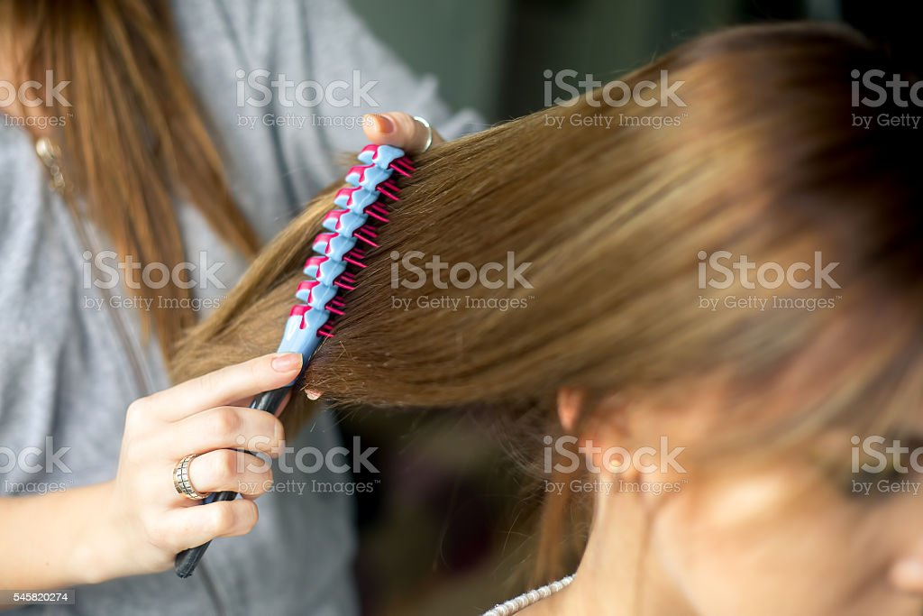 Closeup hairdresser coiffeur makes hairstyle. stock photo