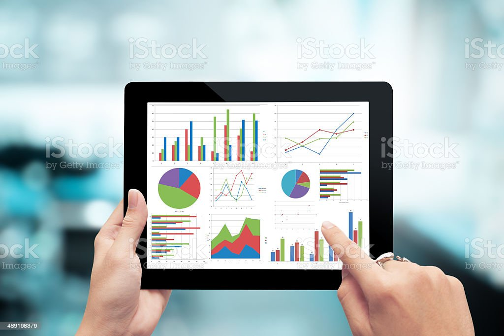 Closeup hand holding digital tablet show analyzing graph stock photo