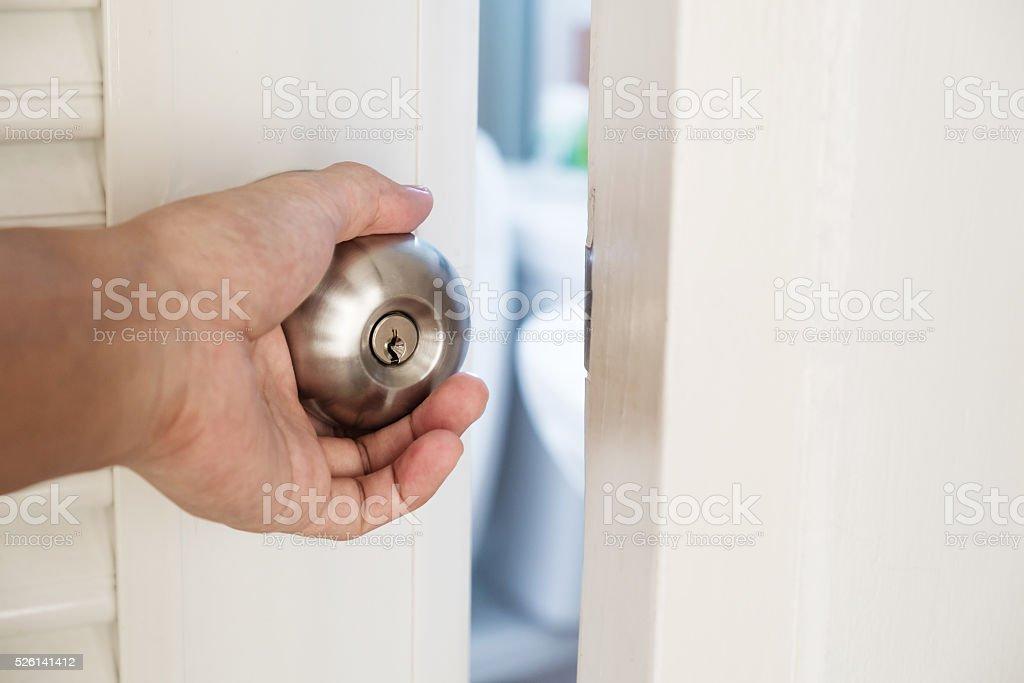 Close-up hand holding door knob, opening door slightly, selective focus stock photo
