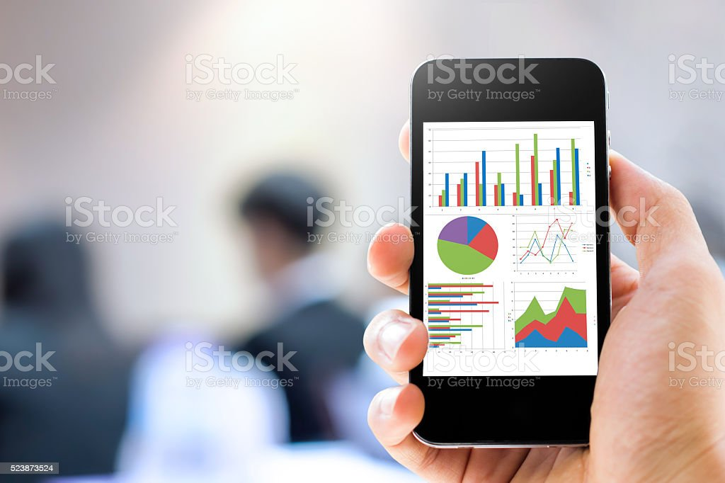 Close-up hand holding mobile phone with analyzing graph stock photo