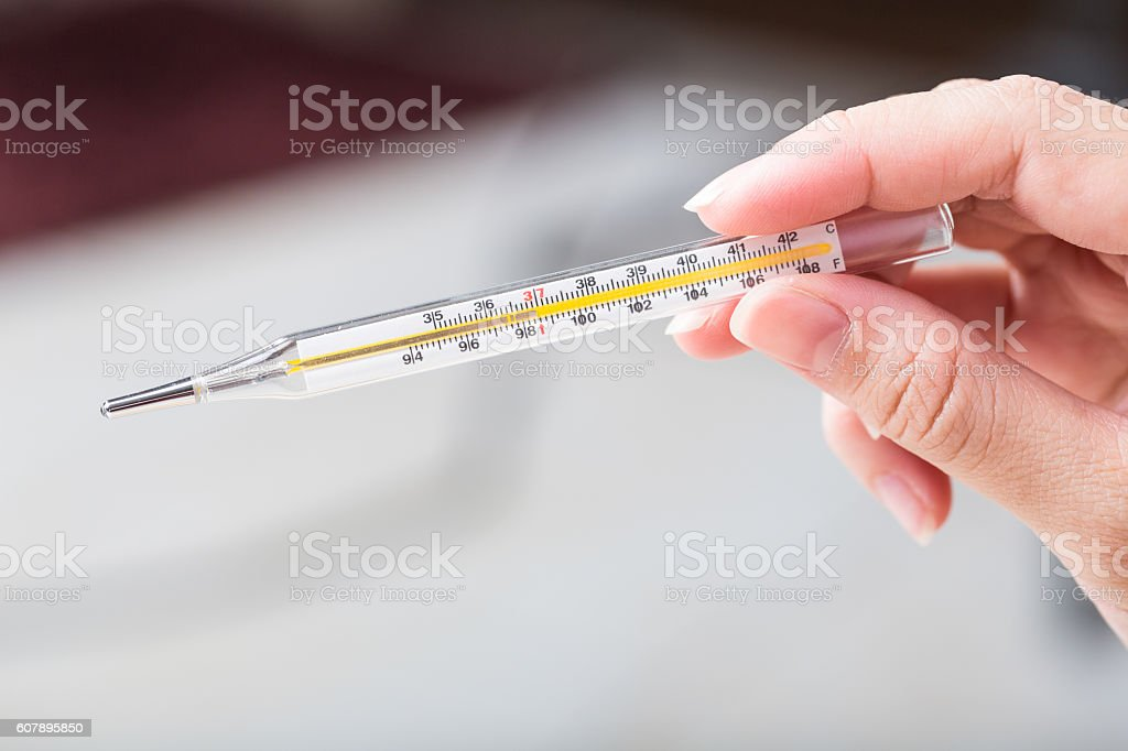 Close-up hand holding on thermometer for checking patient. stock photo