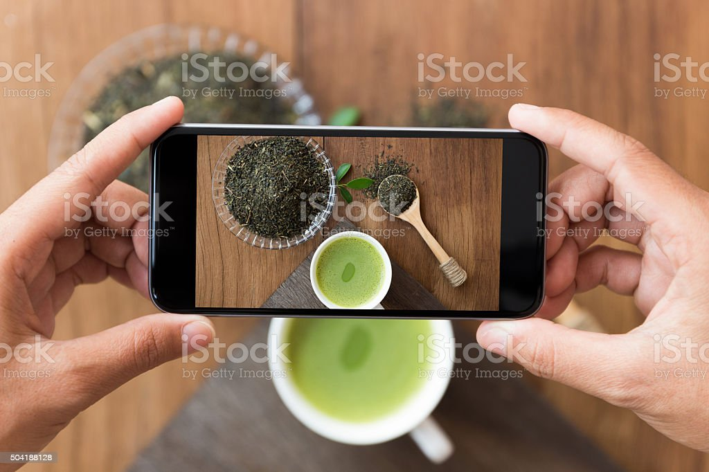 closeup hand holding phone shooting drink photograph stock photo