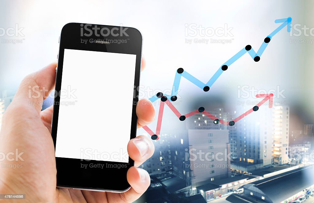 Close-up hand holding smart phone with business graph background stock photo