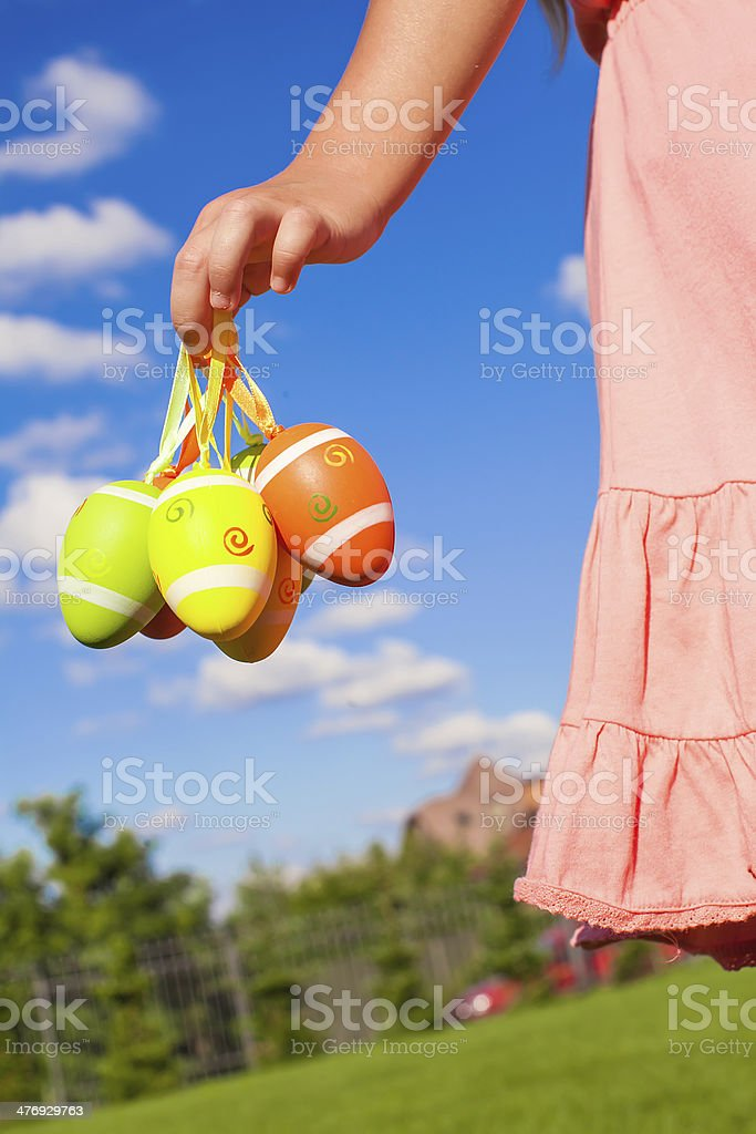 Closeup hand of little girl holding colorful Easter eggs stock photo