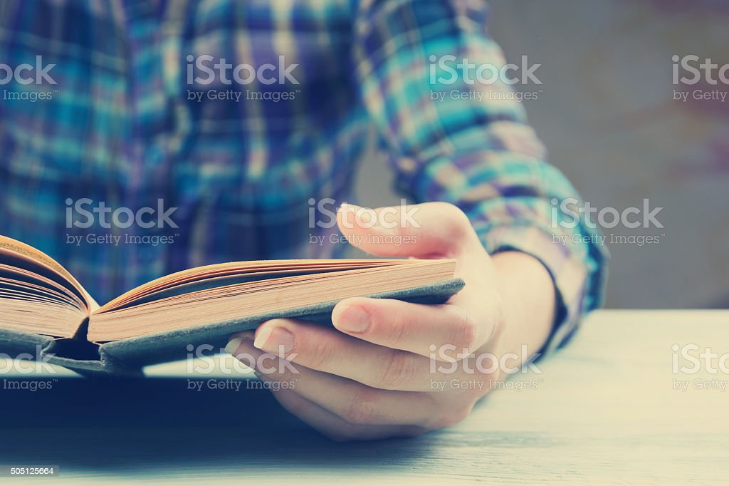 Closeup hand open book for reading concept background. Toned image stock photo