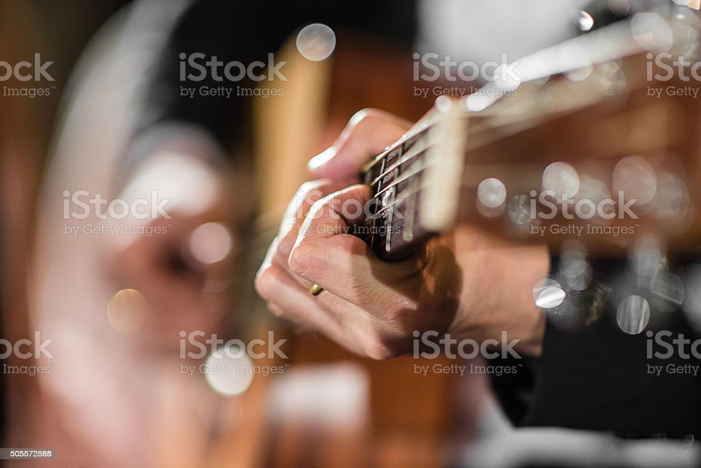 Closeup hand playing acoustic guitar stock photo
