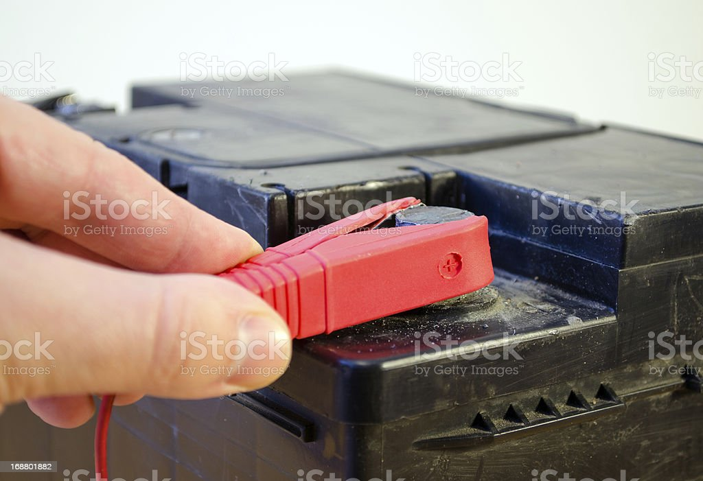 closeup hand plug car battery red clamp plus royalty-free stock photo