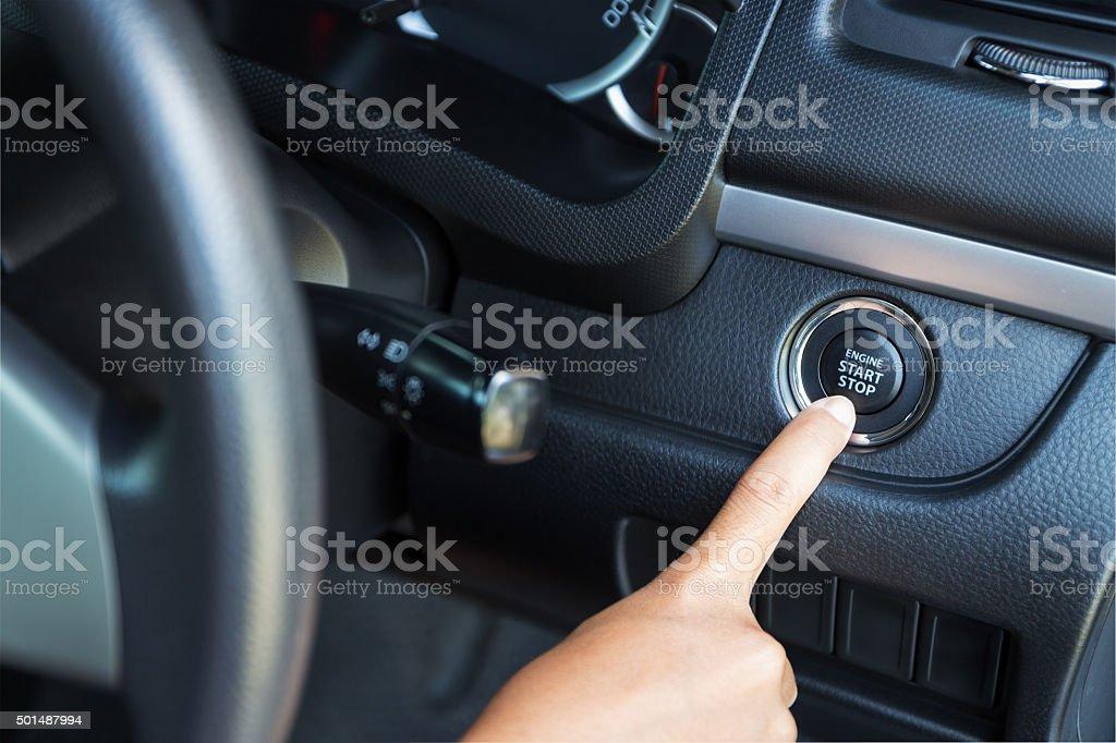closeup hand pushing on car start engine stock photo