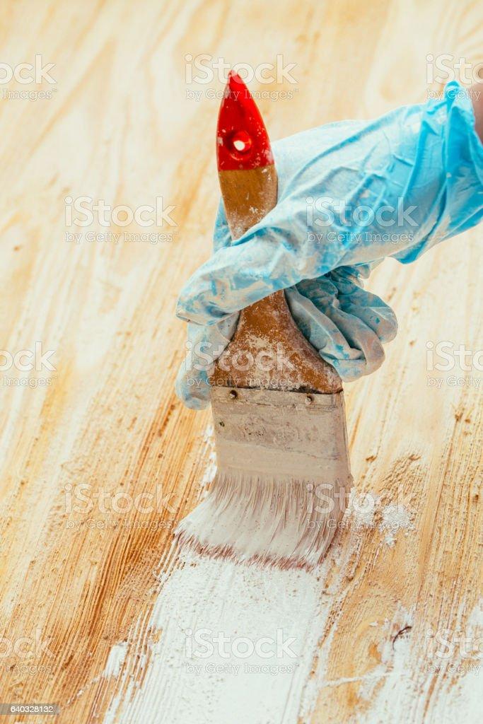 closeup hand use brush paint white on wood surface stock photo