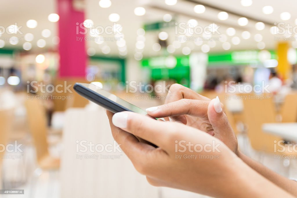 closeup hand using smart phone in department store urban lifestyle stock photo