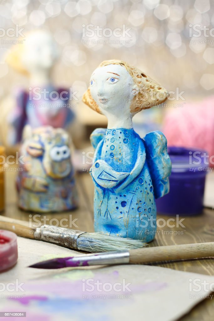 Closeup handmade figurine of Angels from clay pottery and paitbrushes. Selective focus. stock photo