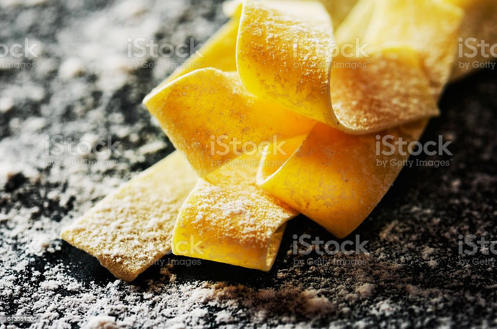 close-up handmade pasta diagonal on a dark with flour background stock photo