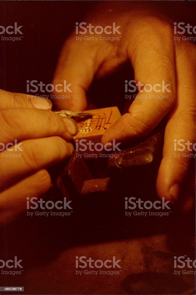 Close-up hands carving a Chinese Chop stamp stock photo