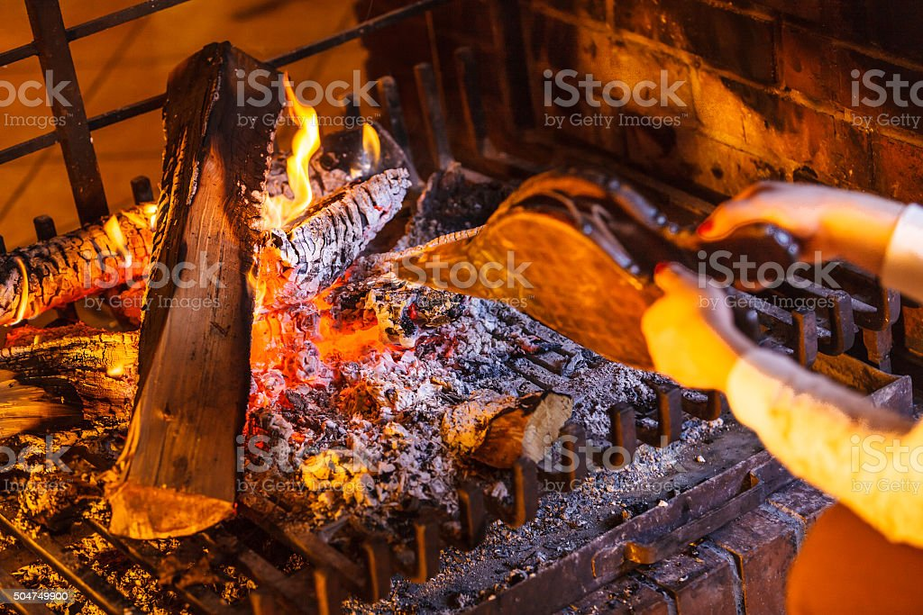 Closeup hands fireplace making fire with bellows. stock photo