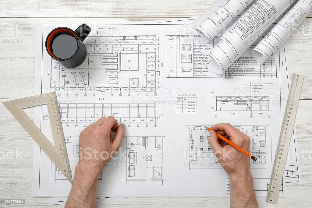 Close-up hands of architect working with pencil on a stock photo