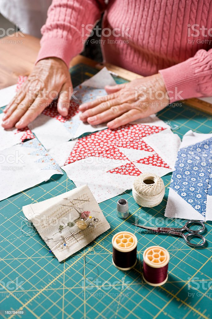 Close-up hands of senior woman sewing quilt royalty-free stock photo