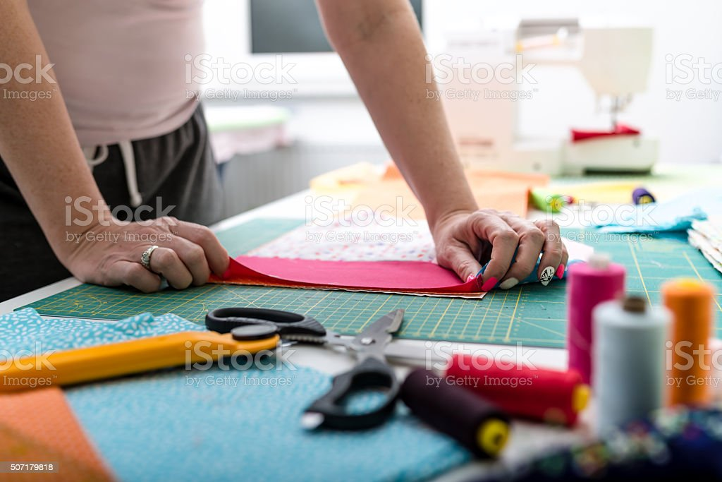 Close-up hands of woman sewing quilt stock photo