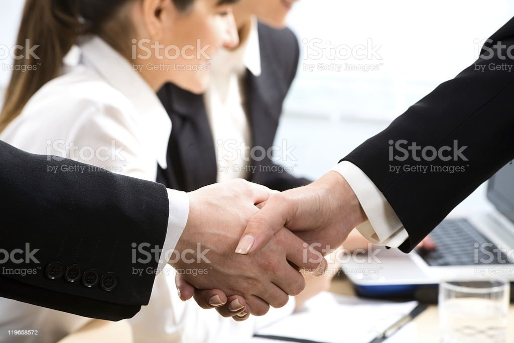 Closeup handshake with workers at laptop in background royalty-free stock photo