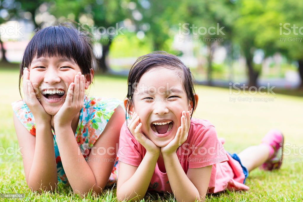 closeup happy little girls on the grass stock photo