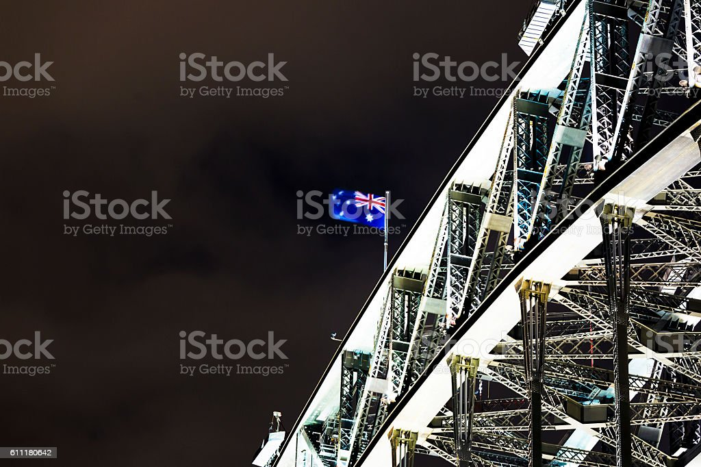 Closeup Harbour Bridge with Australian flag at night, copy space stock photo