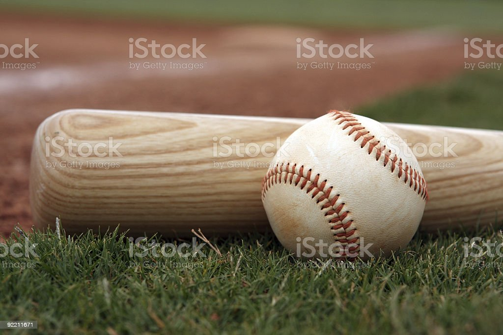 Close-up if baseball and bat resting on the field stock photo