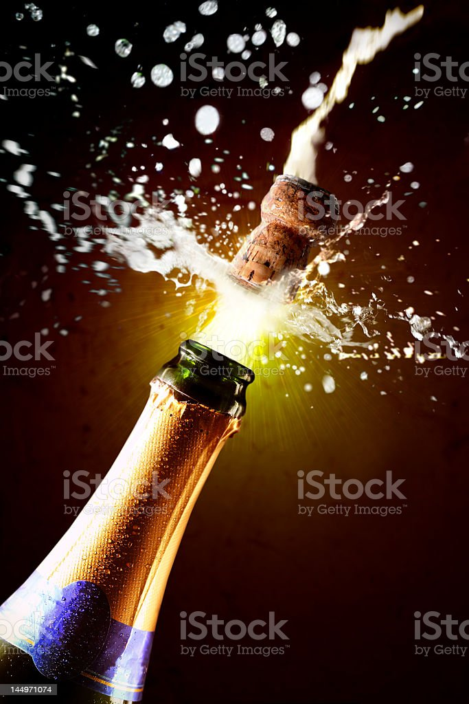 A close-up image of a champagne bottle being popped stock photo